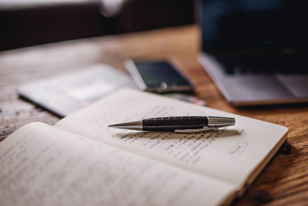 Fotografía de una libreta que tiene un bolígrafo encima. Da la sensación de trabajo.