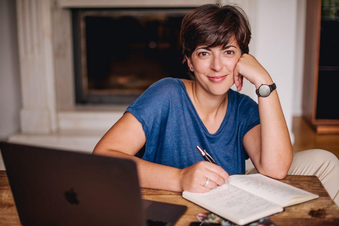 Retrato de una mujer que sonríe a cámara. Morena con el pelo corto y una camiseta azul.