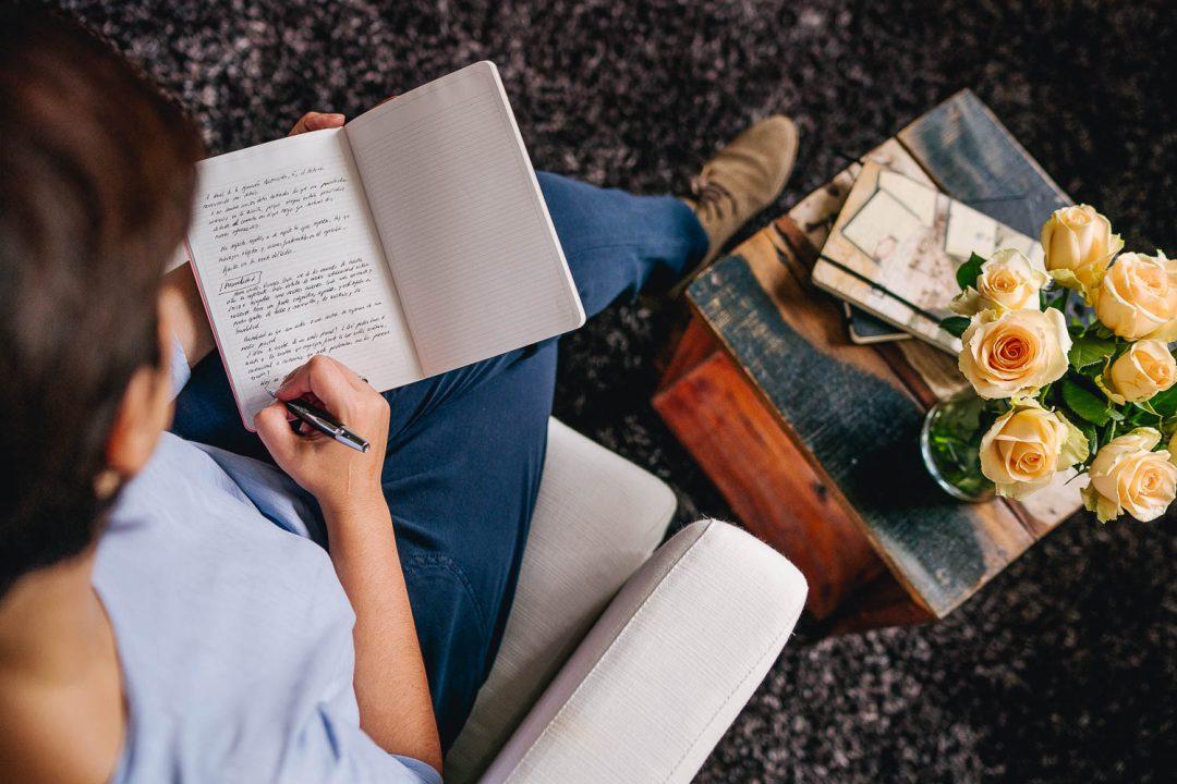 Fotografía cenital de una mujer que está escribiendo en una libreta. A su lado tiene un ramo de rosas blancas.