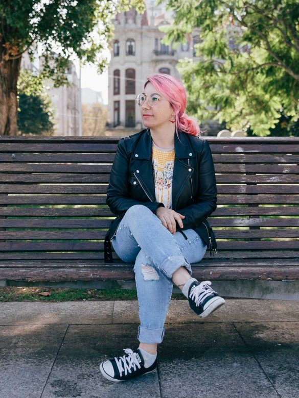 Chica con el pelo rosa sentada en un banco.