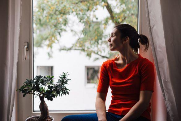 Mujer sentada en el alféizar de una ventana mirando hacia el exterior.