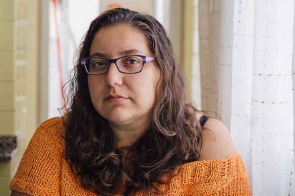 Mujer con gafas y pelo largo mirando a la cámara. Está seria, con expresión dura.
