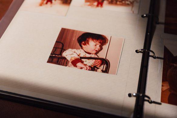 Fotografía de un álbum de fotos antiguo. Se ve la foto de una niña en su cuna de barrotes de aluminio.