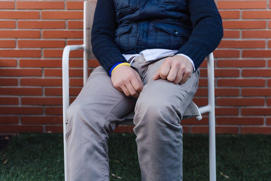Un hombre sentado en una silla, no le vemos la cara, solo las manos y las piernas.