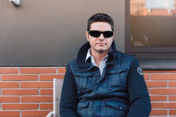 Retrato de un hombre invidente sentado en una terraza.