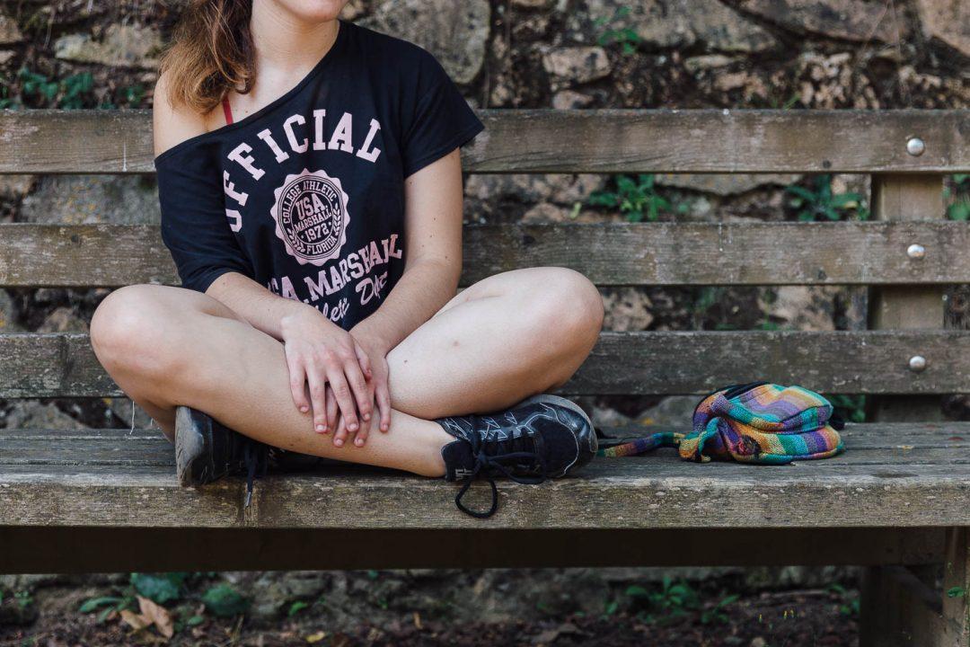 Chica joven sentada en un banco con las piernas cruzadas.
