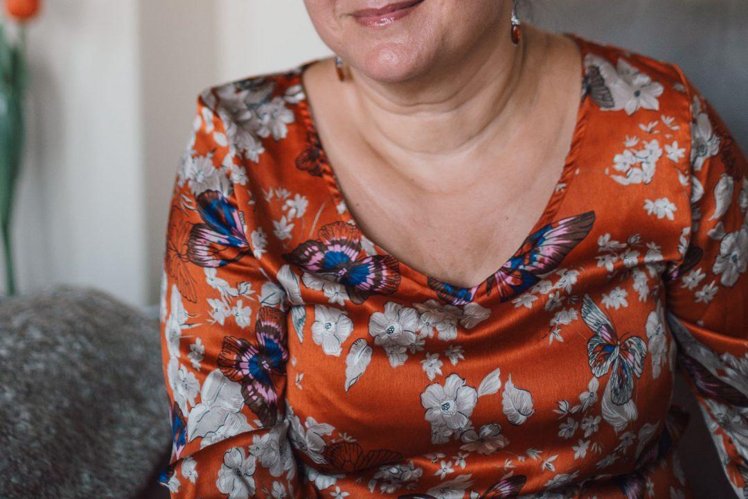 Retrato de una mujer a quien no se le ve la cara. Lleva una camiseta naranja con flores y mariposas.