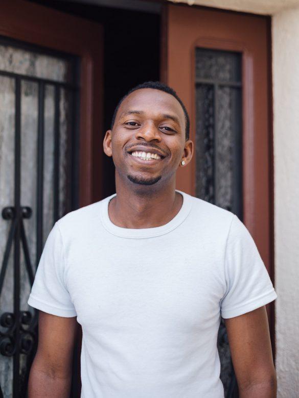 Hombre africano delante de la puerta de su casa, sonríe hacia la cámara.