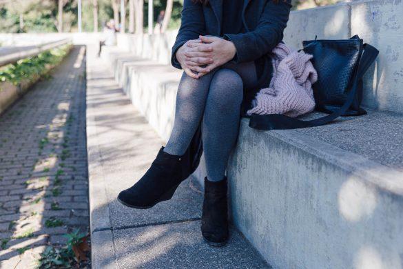 Fotografía de una mujer a la que no se le ve la cara, está sentada en unas escaleras de un parque, se coge la pierna con las manos cruzadas. Se encuentra en una zona de penumbra, los reflejos del sol se escapan entre los árboles como lo hace su enfermedad invisible, la colitis ulcerosa.