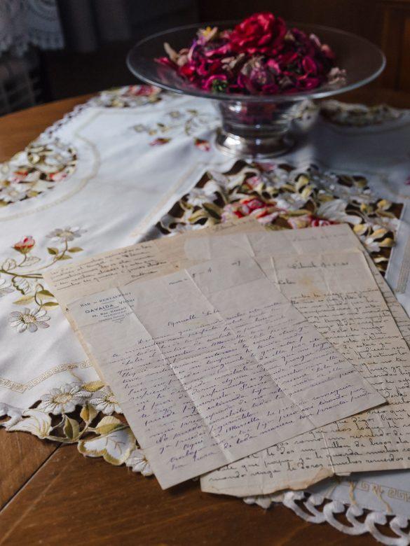 Mesa cubierta por un tapete y encima de este hay unas cartas antiguas, escritas en la posguerra. También aparece un centro lleno de pétalos secos de rosas rojas.