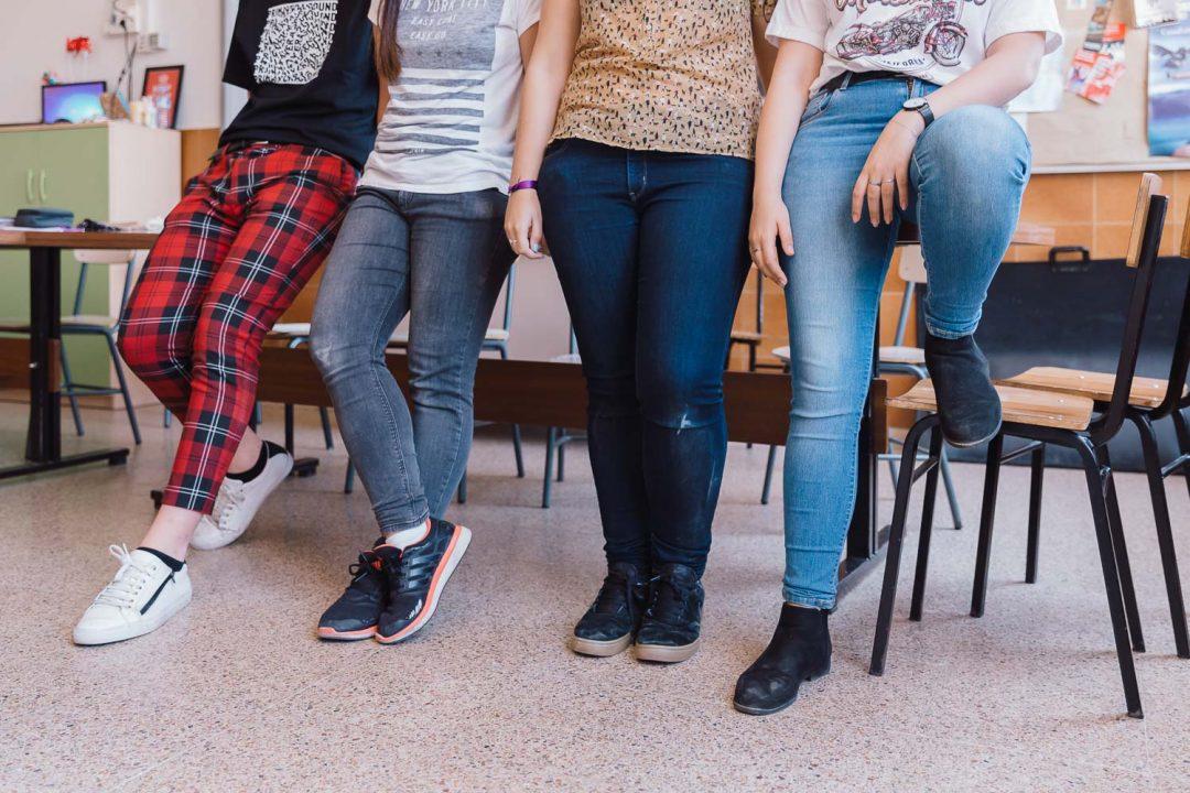 Foto de cintura hacia abajo de cuatro jóvenes apoyados en una mesa. Cada uno con su estilo, pantalones a cuadros, vaqueros, pantalones rotos.