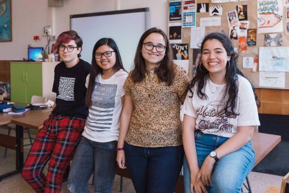 Tres chicas morenas con el pelo largo y un chico con un mechón teñido en rojo sonríen mirando a cámara. Están sentados en una mesa del aula de arte.