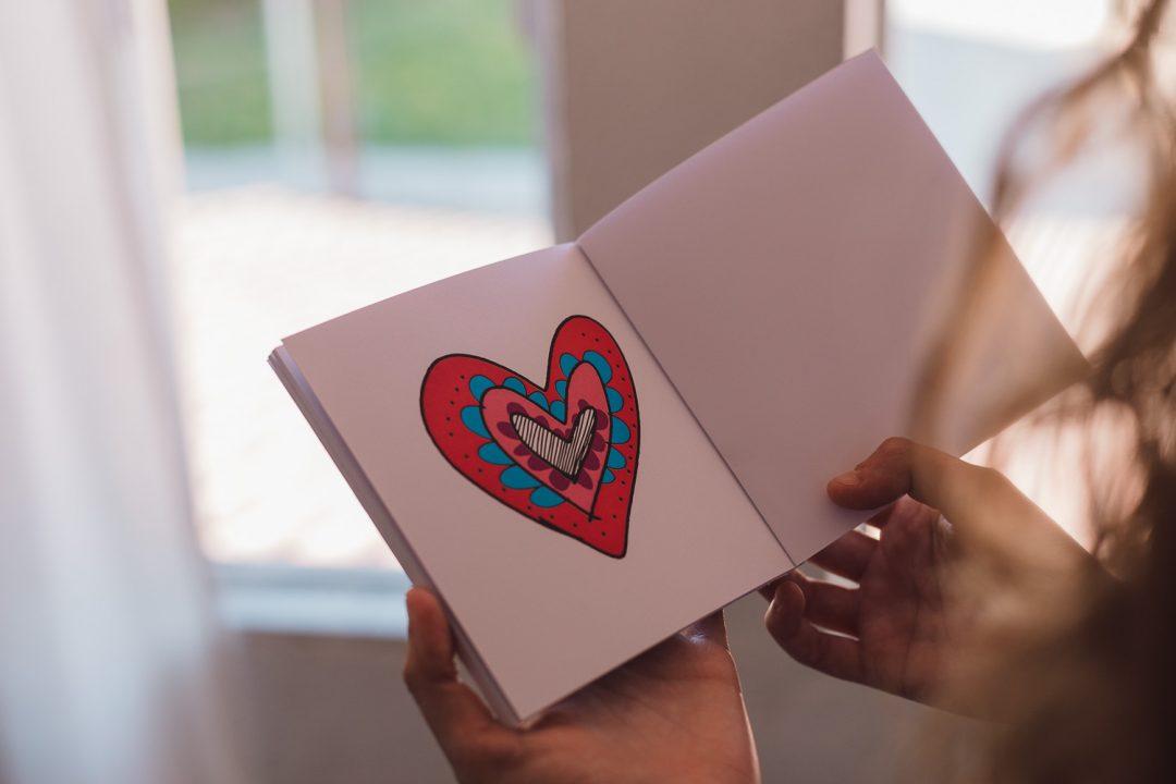 Las manos de Miriam nos muestran la página donde sale un corazón dibujado y pintado de colorines.