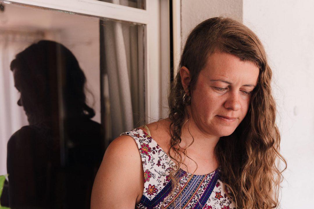 Miriam mira hacia bajo, con la cara pensativa y detrás suyo se refleja su silueta en una ventana que hace pensar en los problemas que carga a su espalda.